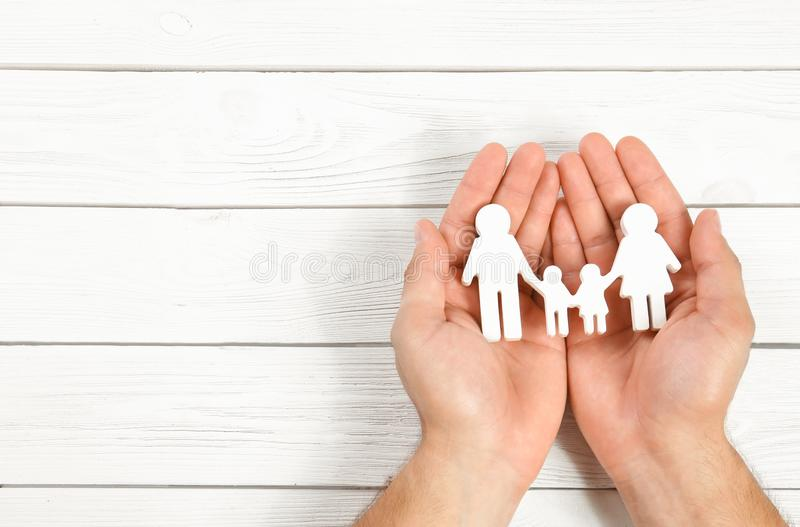 Young man holding family figure in his hands  white wooden background, top view. Space for text. Young man holding family figure in his hands against white royalty free stock images