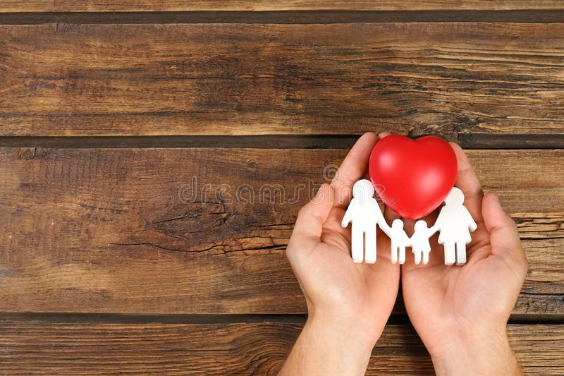 Young man holding  figure and red heart in his hands on wooden background, top view. Space for text. Young man holding family figure and red heart in his hands royalty free stock image
