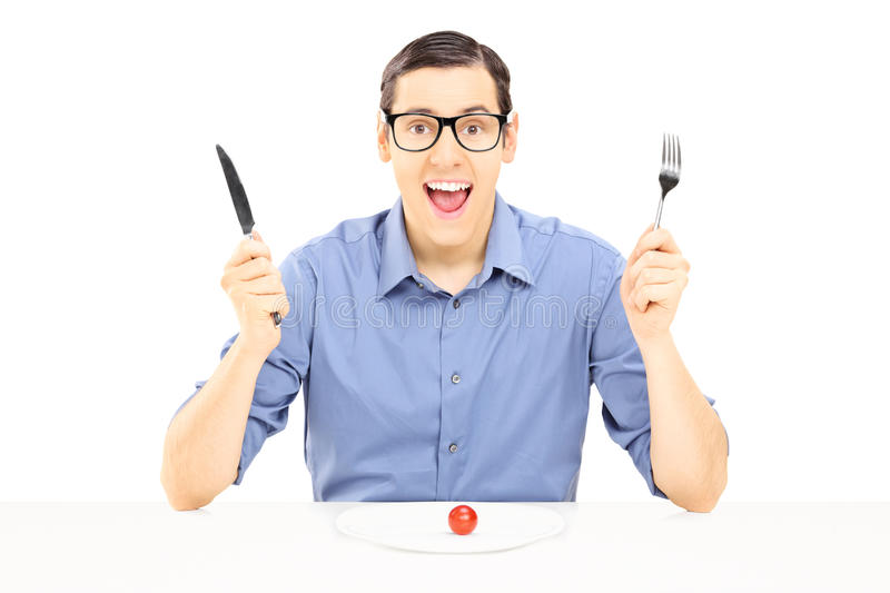 Young man holding a fork and spoon eating cherry tomato stock photos