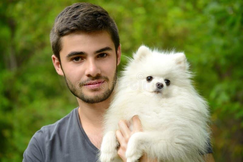 Young man holding german spitz puppy. Attractive young man holding german spitz puppy outside and looking at camera royalty free stock photos