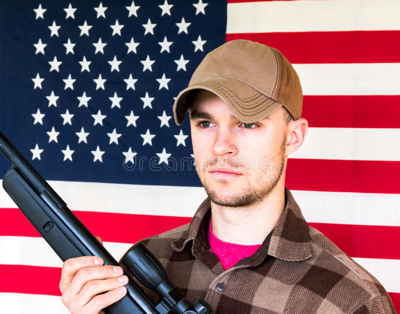 Young Man Holding Gun on American Flag Background stock photos