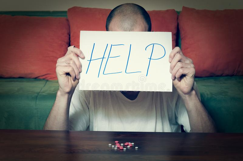 Young man holding help sign written letters on paper with strong medicament pills in front of him addict suicidal concept stock photography