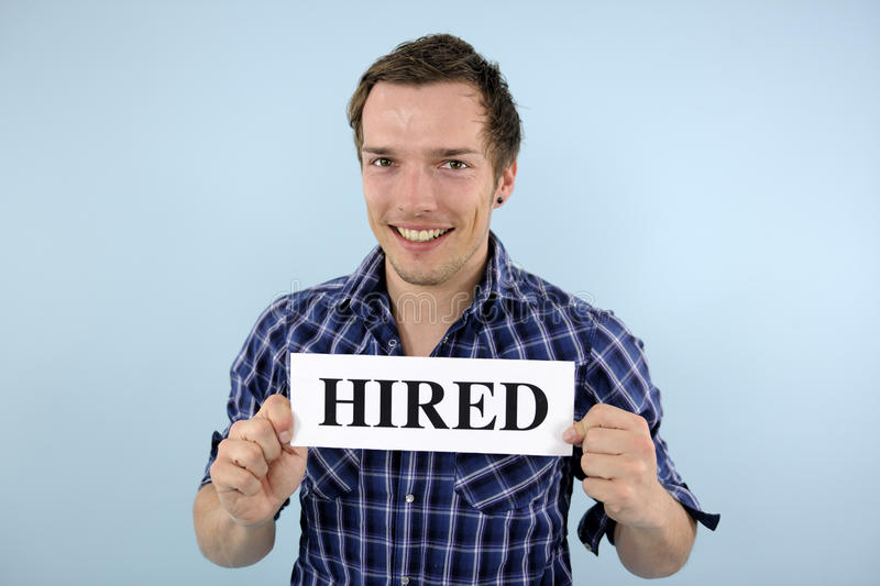 Young man holding hired sign. Happy young man holding hired sign stock image