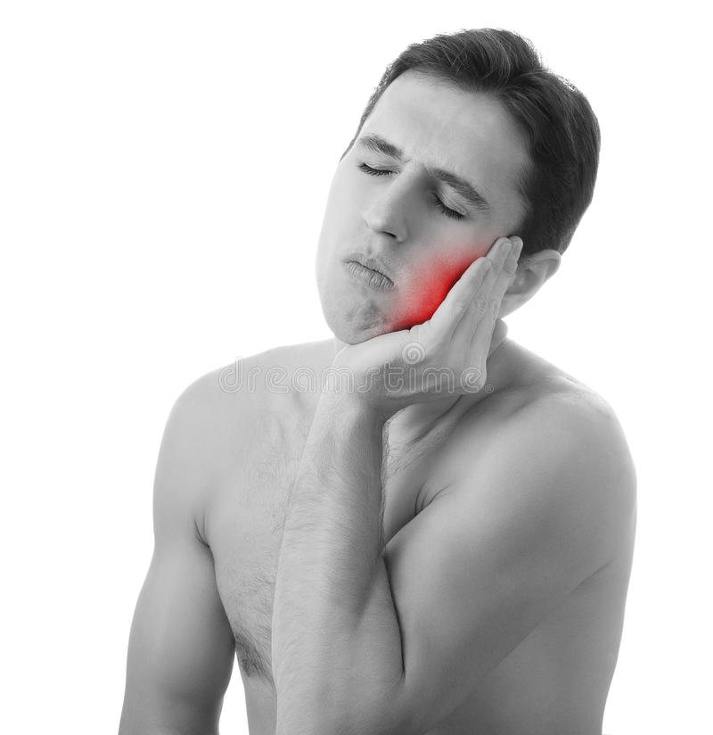 Young man holding his aching tooth in pain, stock photo
