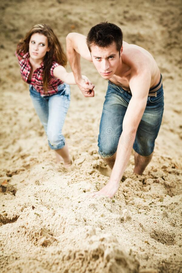 Young man holding his girfriend by hand and going up on sandy hill. Young men holding his girfriend by hand and going up on sandy hill on summer day. Love stock photo