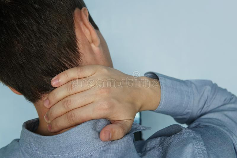 Young man is holding his neck. the concept of health, pain in the neck. The patient complains of a sore neck stock photography