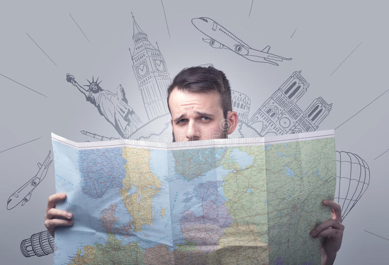 Young man holding map. Handsome young man holding a map with famous sightseeing destinations above his head stock image