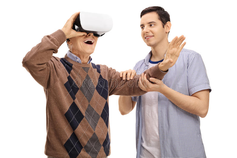 Young man holding a mature man hand while he is using a VR h. Young men holding a mature men hand while he is using a VR headset isolated on white background royalty free stock photos