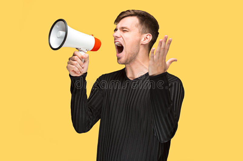 The young man holding a megaphone. On on yellow studio background stock photos