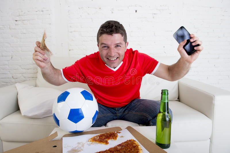 Young man holding mobile phone and money in his hands watching fottball game on television internet gambling concept. Young man holding mobile phone and money in royalty free stock image