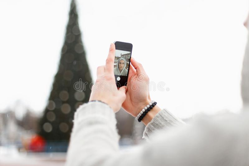 Young man holding a mobile phone and takes pictures himself stock photos