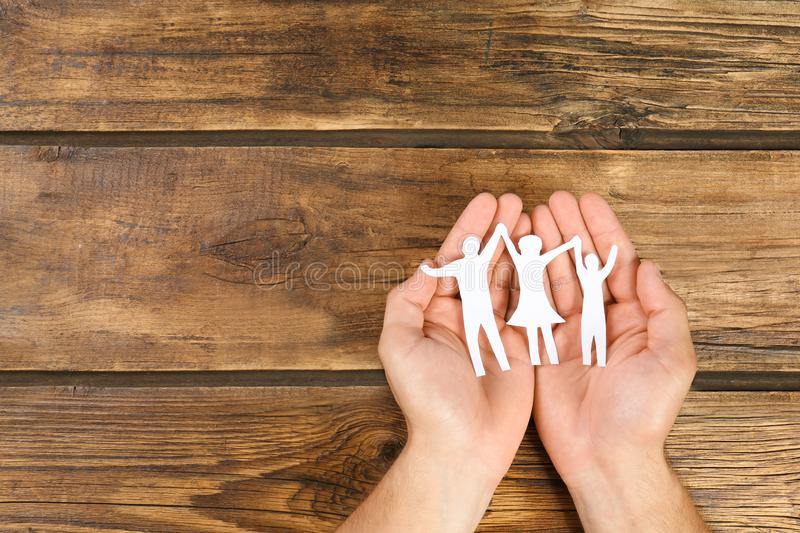 Young man holding paper family figure in his  against wooden background, top view. Space for text. Young man holding paper family figure in his hands against royalty free stock photos