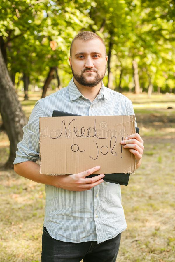 Young man holding piece of cardboard with text NEED JOB outdoors. Bussines concept royalty free stock photos