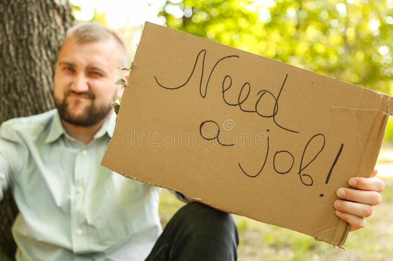 Young man holding piece of cardboard with text NEED JOB outdoors. Bussines concept stock image