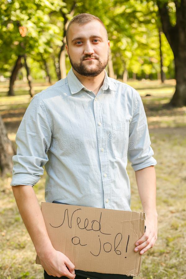 Young man holding piece of cardboard with text NEED JOB outdoors. Bussines concept stock photo