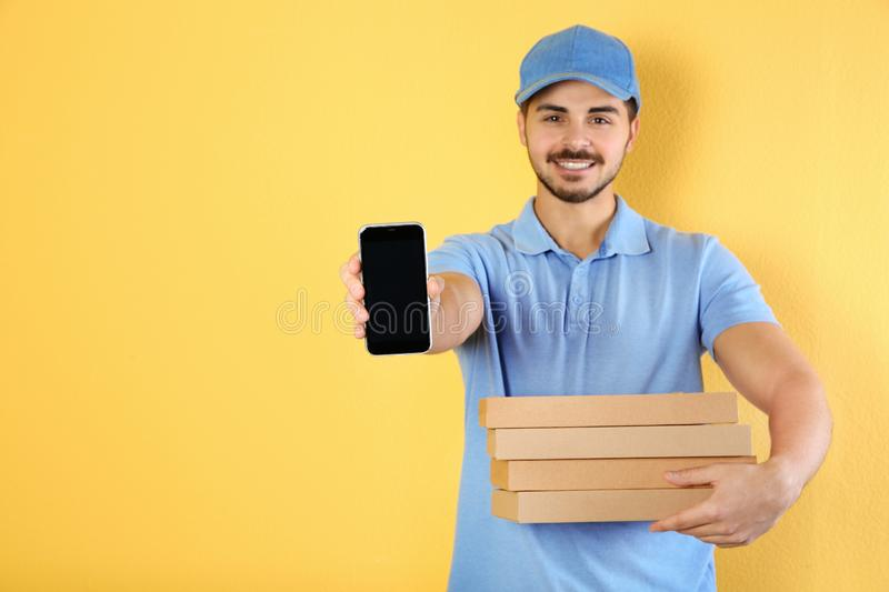 Young man holding pizza boxes and smartphone on color background, mockup for design. Food delivery royalty free stock images