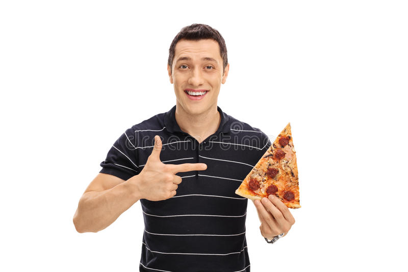 Young man holding a pizza slice. And pointing at it isolated on white background royalty free stock photos