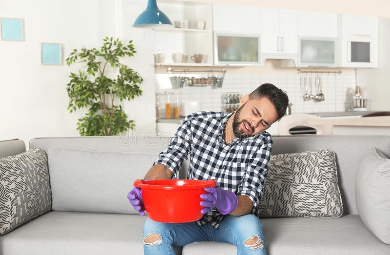 Young man holding plastic basin under water leakage from ceiling and calling plumber. At home stock image