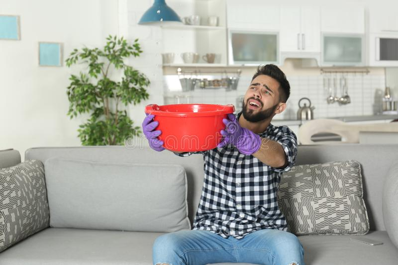 Young man holding plastic basin under water leakage from ceiling at home. Plumber service royalty free stock images