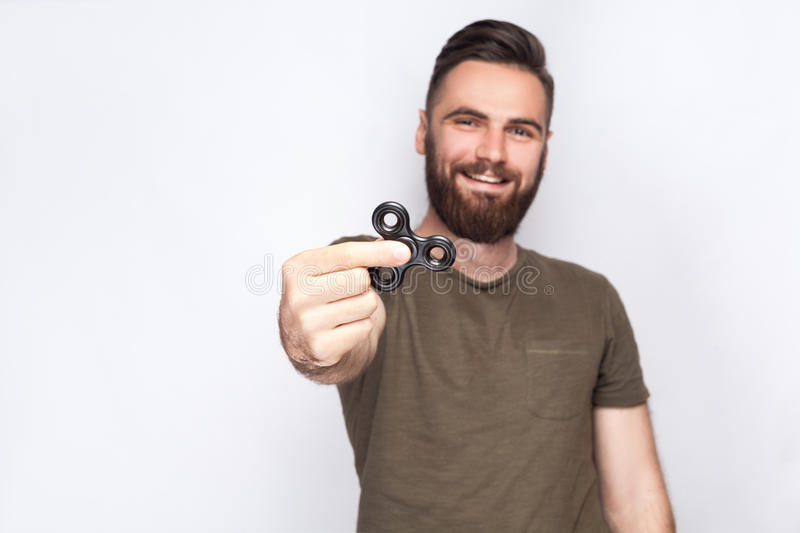 Young man holding and playing with fidget spinner. stock photo