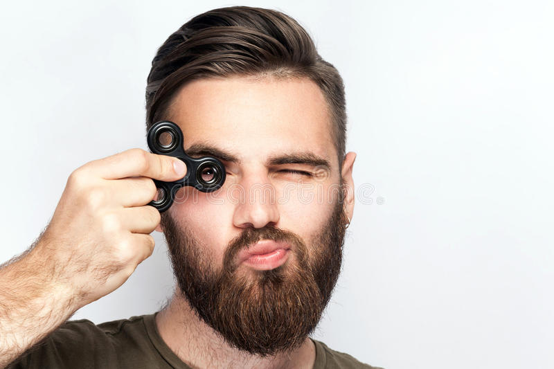 Young man holding and playing with fidget spinner. Studio shot on white background stock image
