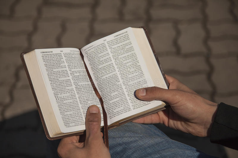 Young man holding and reading holy bible stock photo