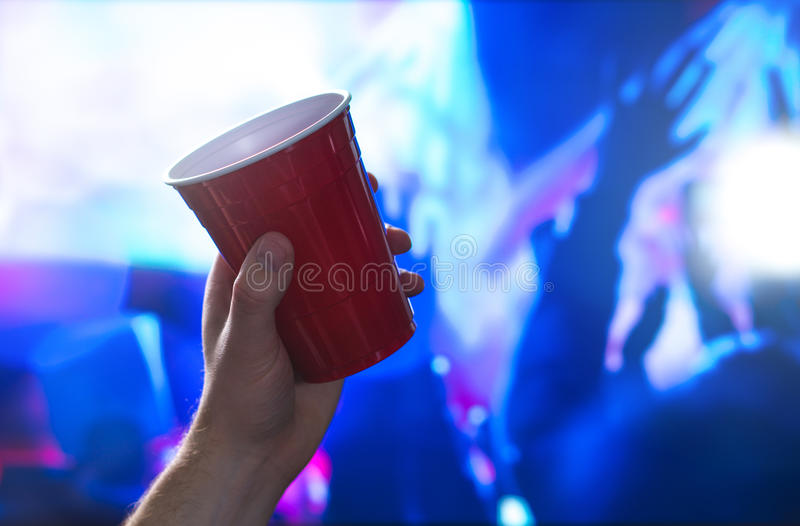 Young man holding red party cup in nightclub dance floor. Alcohol container in hand in disco. College student having fun. Young man holding red party cup in royalty free stock photo