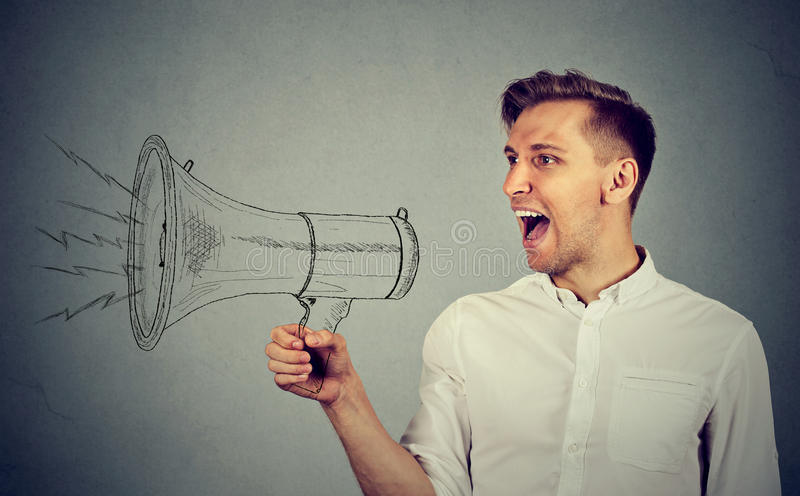 Young man holding screaming in megaphone. Portrait angry young man holding screaming in megaphone on grey wall background. Negative face expression emotion royalty free stock photo