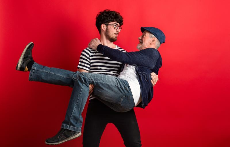 Young man holding senior father in a studio on red background. stock images