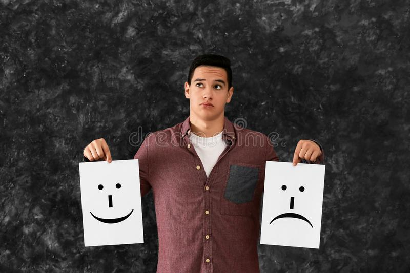 Young man holding sheets of paper with drawn emoticons on grey background stock images