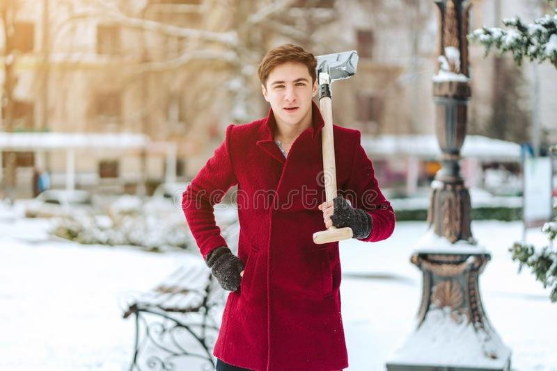 Young man holding shovel outdoors royalty free stock images