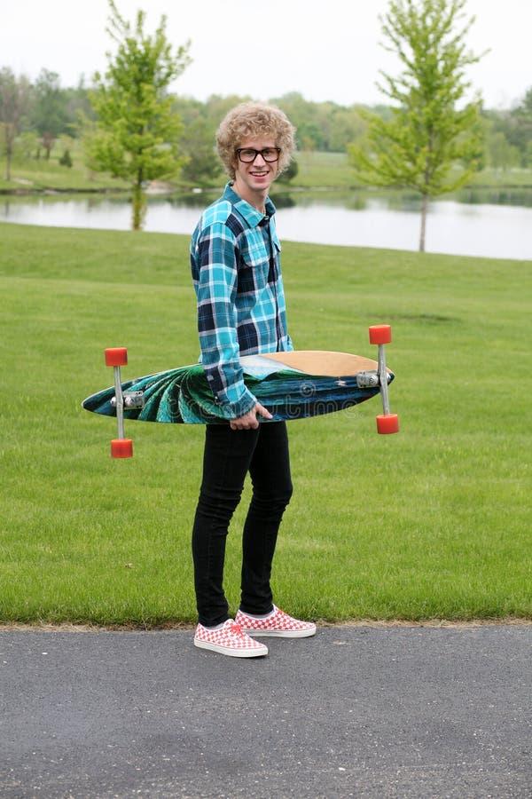 Young man holding skateboard stock photos