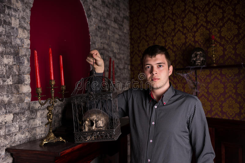 Young Man Holding Skull in Cage Inside Castle stock photo