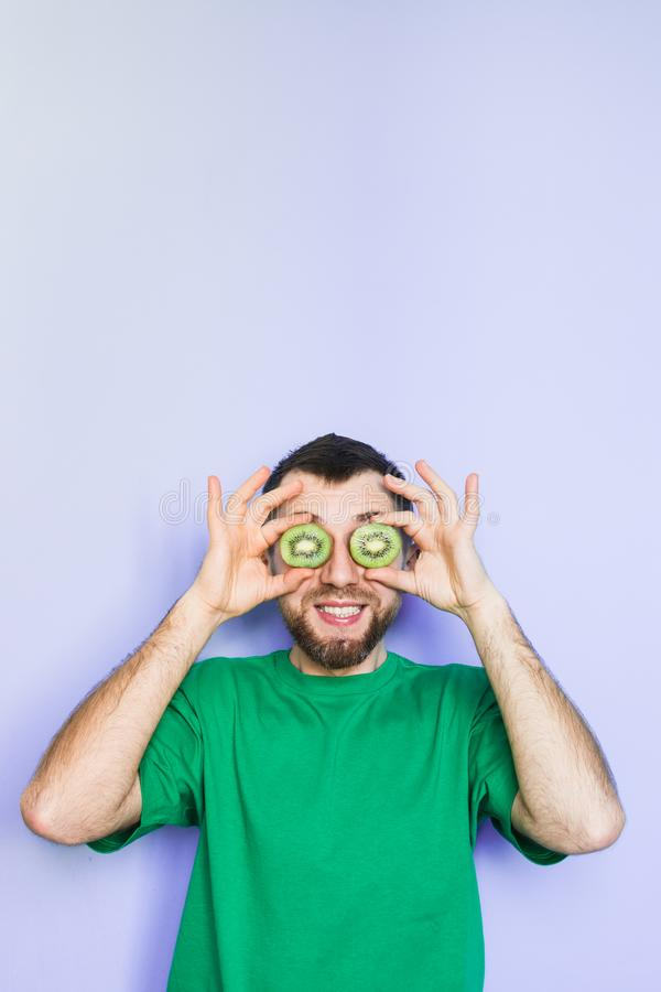 Young man holding slices of kiwi in front of his eyes royalty free stock photography