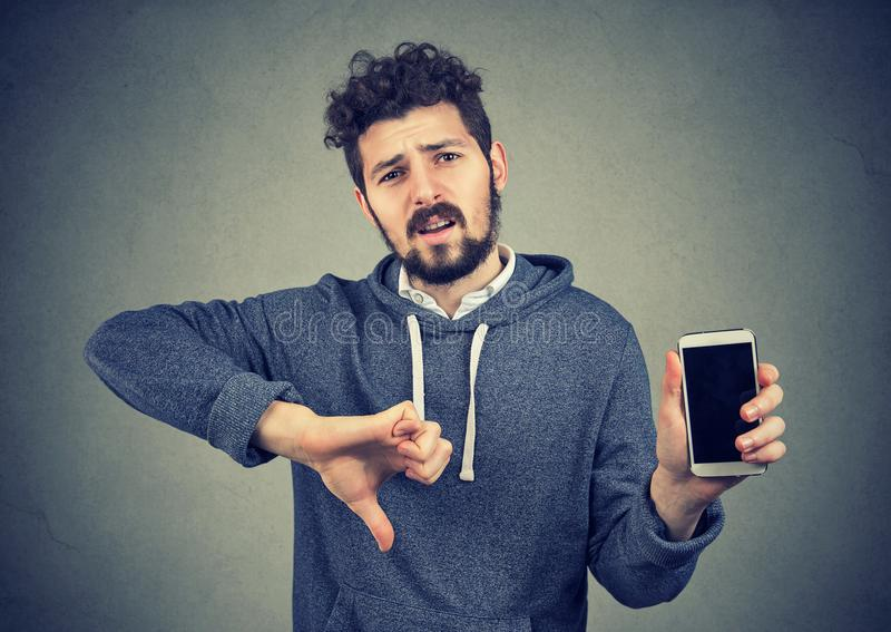 Man dissatisfied with quality of gadget royalty free stock photography