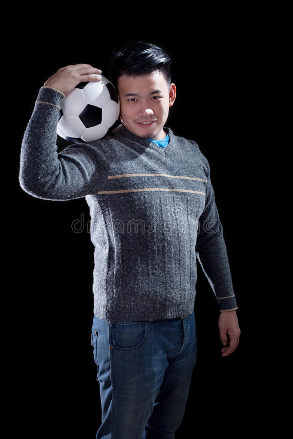 young man holding soccer football with smiling face standing against black background use for people and sport hobby royalty free stock photos