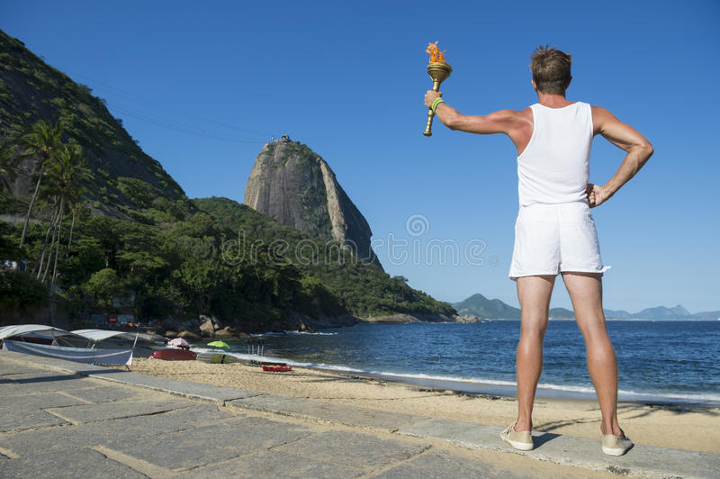 Young Man Holding Sport Torch Rio de Janeiro. Young athletic man standing with sport torch facing the Rio de Janeiro Brazil skyline with Sugarloaf Mountain at stock images