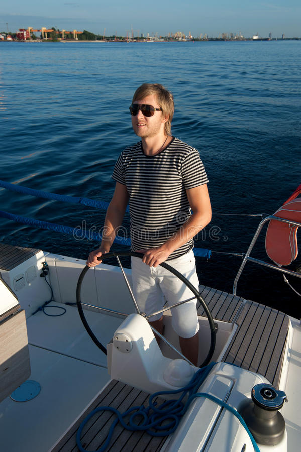 Download Young Man Holding Steering Wheel Of The Yacht Stock Image - Image of deck, hand: 34300923