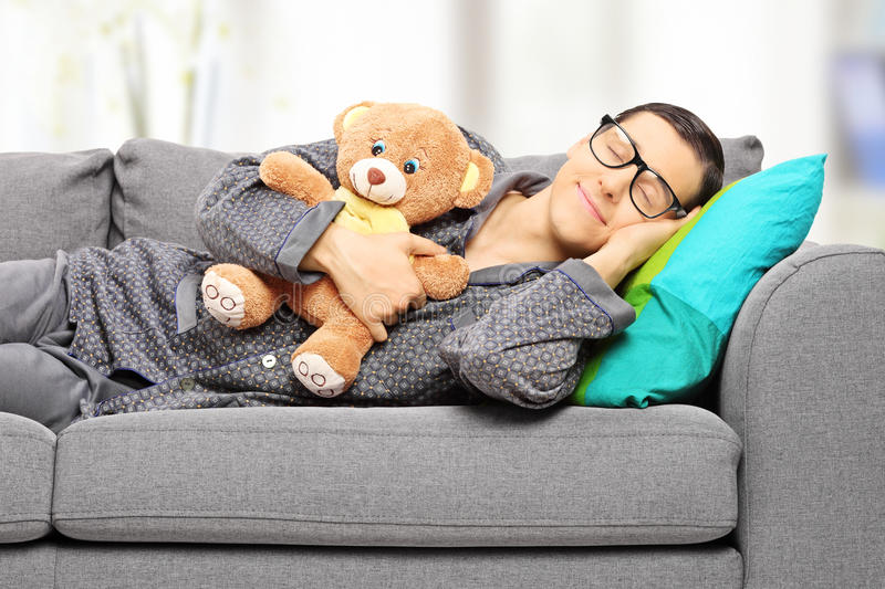 Young man holding teddy bear and taking a nap on couch royalty free stock photo