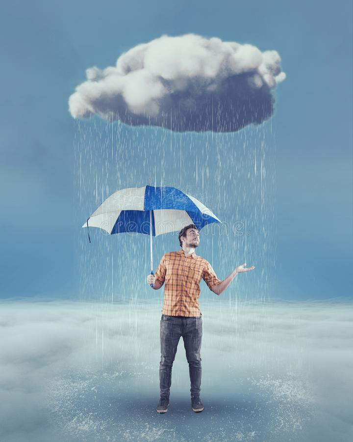 Young man holding an umbrella. Young man holds an umbrella under a rainy cloud and checks if is still raining stock photos