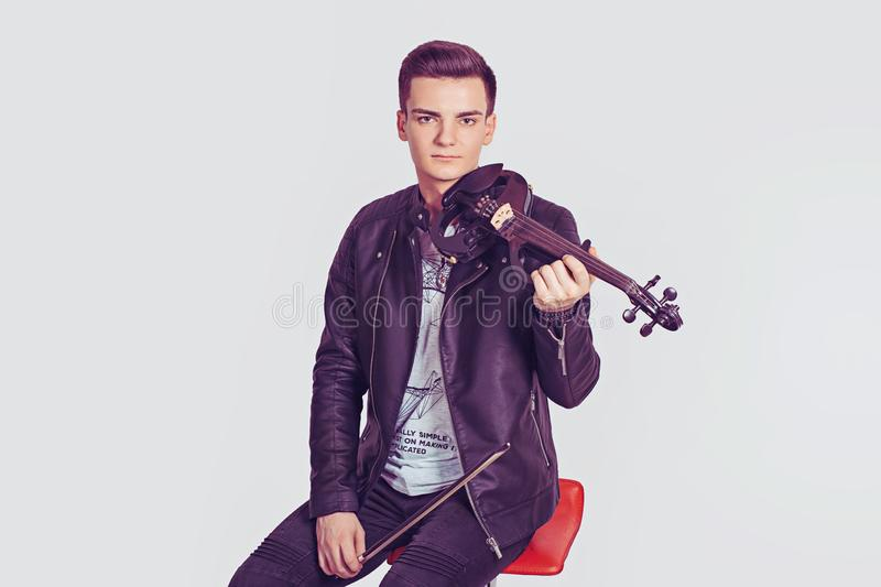 Young man holding violin and fiddlestick stock images
