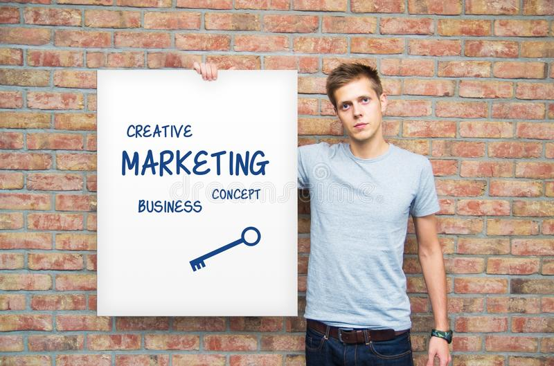 Young man holding whiteboard with marketing content. Business presentation royalty free stock photos