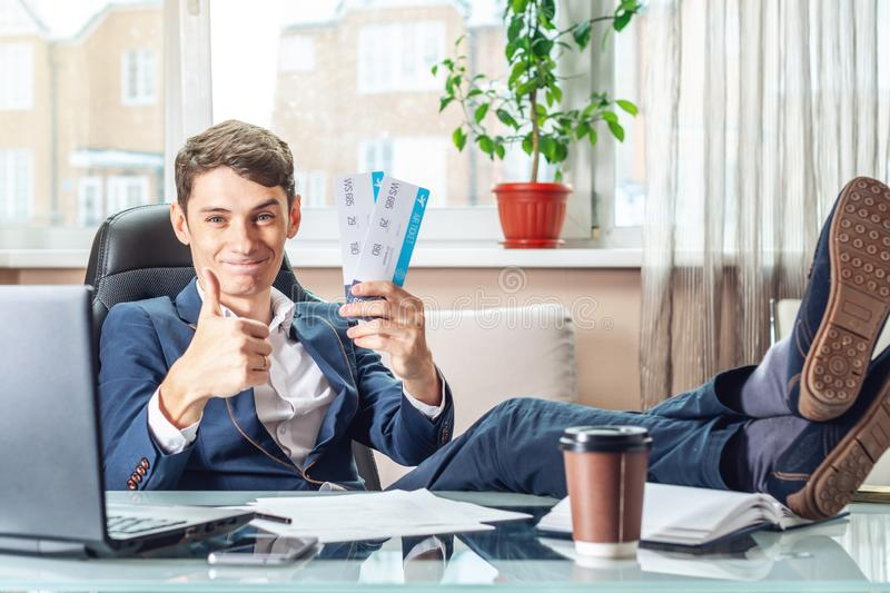 The young man is holding the won tickets. The joy of waiting for the journey. Concept of the office on vacation stock photography