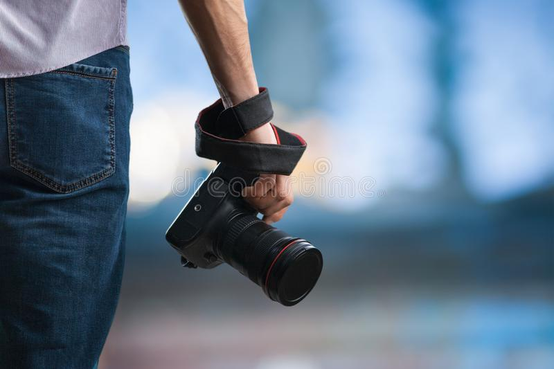 Young man holds black modern digital camera. On natural background royalty free stock photos
