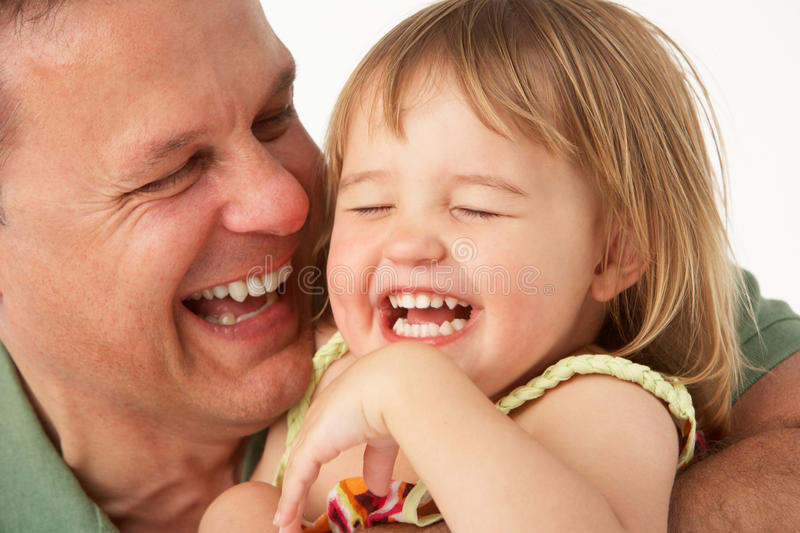 Young man holds child in arms. Smiling stock photography