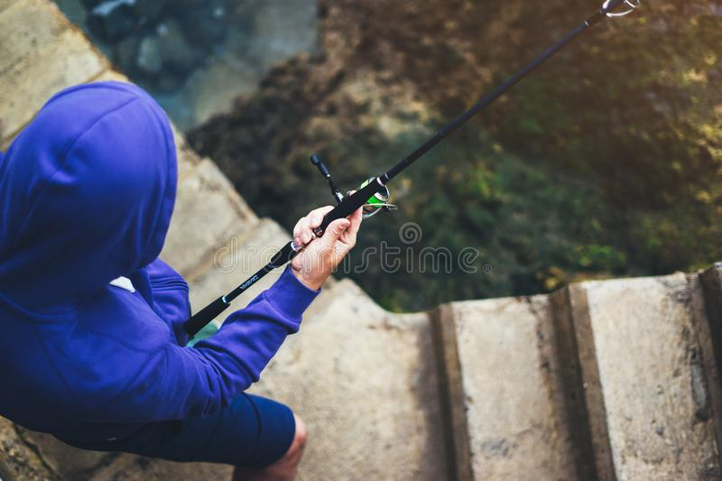 Young man holds a fishing rod and catches fish in the nature on a sea background, hipster fisherman spends vacation on the blue oc royalty free stock image