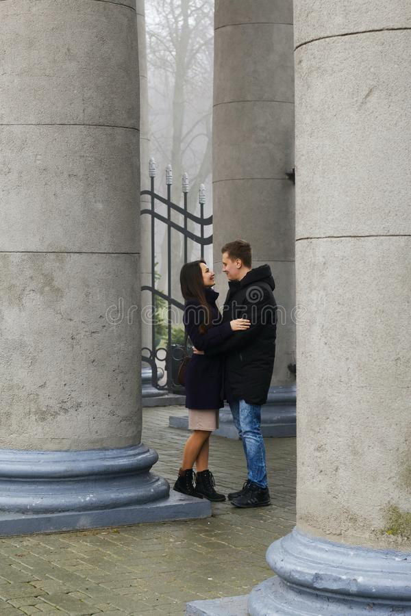 A young man holds a girl by the hands. Look into each other`s eyes. They stand among the large vintage columns. Dressed in a coat stock photography