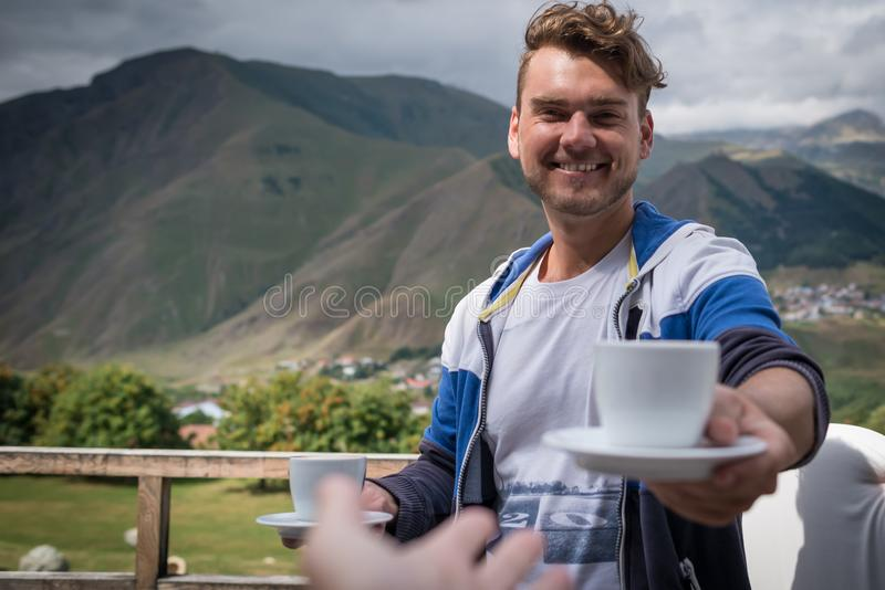 Young man holds out a cup of coffee. Happy guy with drinks in the morning royalty free stock photos