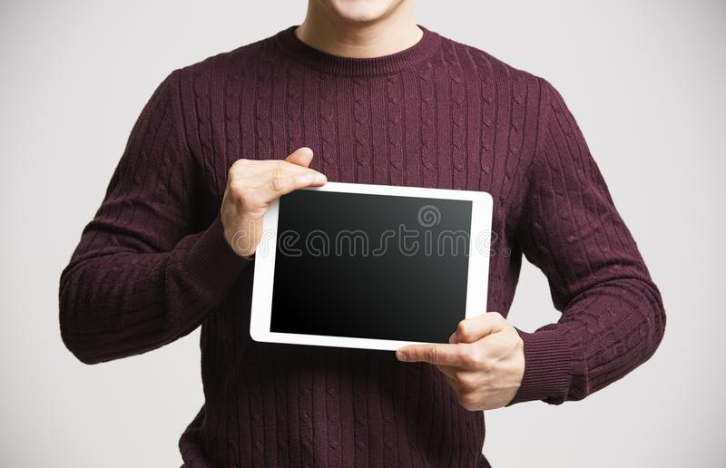 Young man holds a tablet, showing its screen, mid section stock photo