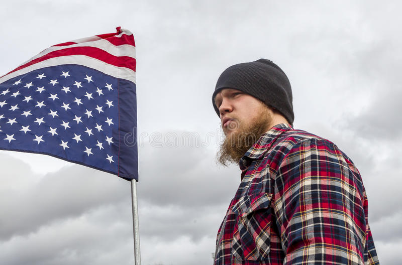 Young man holds upside down flag. royalty free stock image